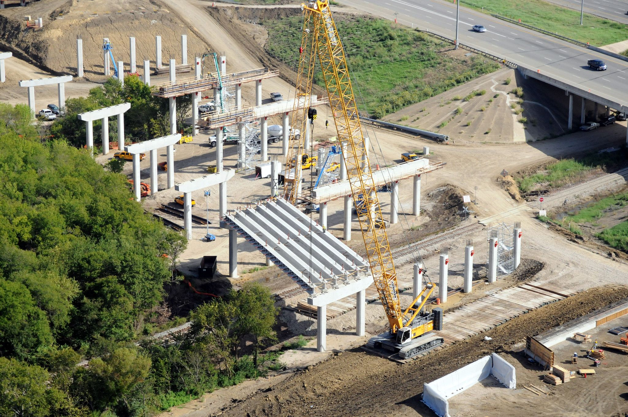 Aerial view of construction crane on a construction site of a highway bridge overpass